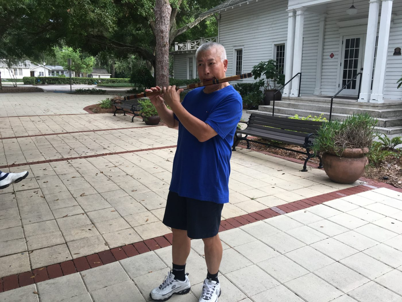 CHangkui Tang playing Dizi, Chinese Transverse Flute, in front of Windermere Town Hall of Windermere, FL (credit: Windermere Sun-Susan Sun Nunamaker)