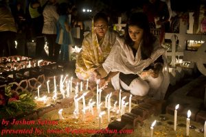 halloween-bangladeshi-girl-and-her-motherlighting-grave-candles-on-the-headstone-of-a-deceased-relative-in-the-city-of-chittagong-for-the-observance-of-allhallowtide, by-jashim-salam