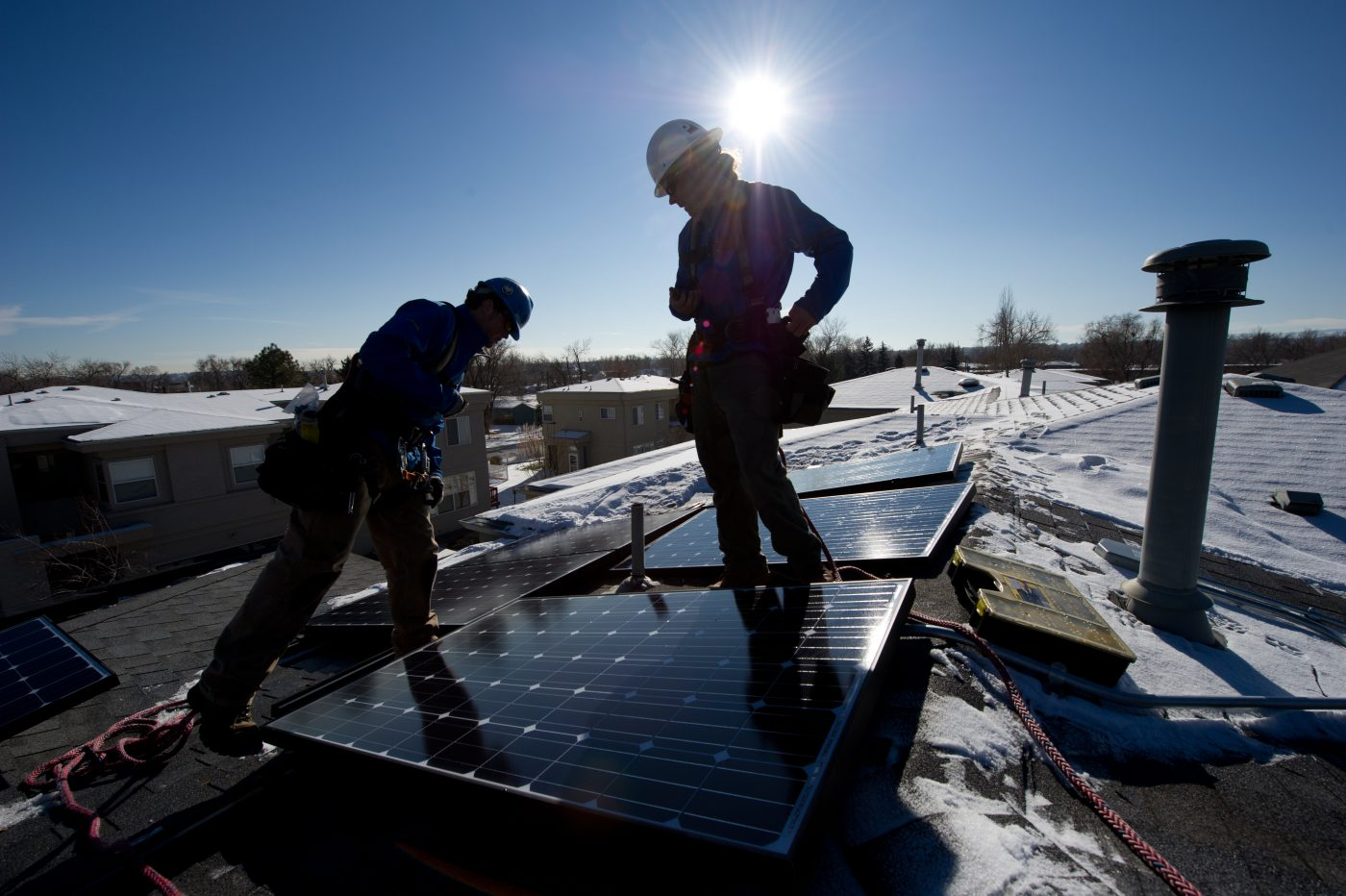 December 19, 2011- Kyle Travis, left and Jon Jackson, with Lighthouse Solar, install microcrystalline PV modules on top of Kevin Donovan's town home. (Photo by Dennis Schroeder)