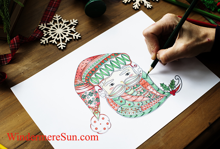 A person drawing a colorful Santa Claus' face