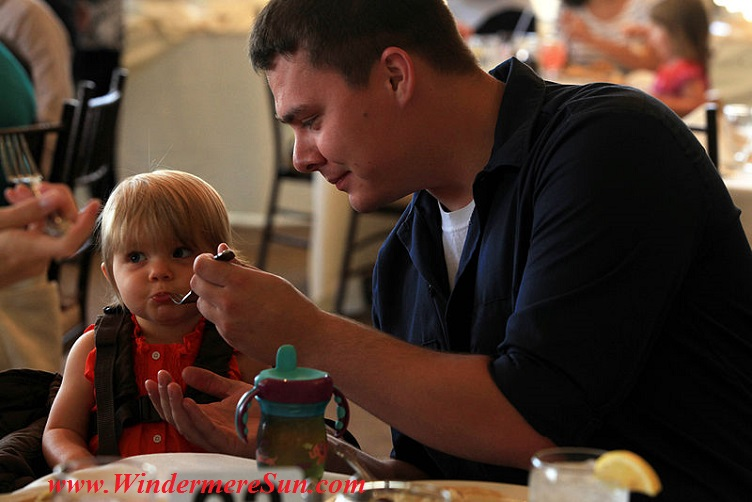 Father and daughter (Petty Officer 3rd Class Arthur Richardson feeding his 1 year old daughter Adalynn Richardson during Father's Day luncheon)